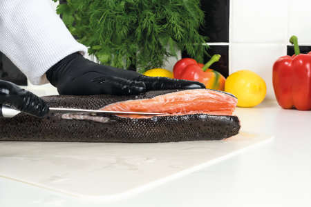 chef cuts raw trout on a white board. Ingredients for the dish lemon, red pepper, green salad