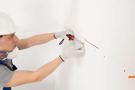 a worker measures the distance between holes in the wall, side view Standard-Bild
