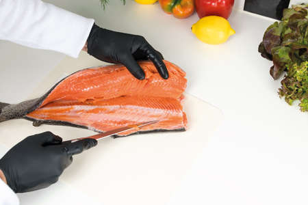 chef cuts raw trout on a white board, top view. Ingredients for the dish lemon, red pepper, green salad