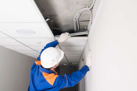 a worker in a helmet finishes the installation of a false ceiling, rear view