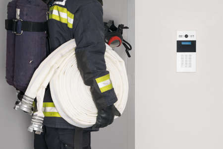 a fireman with a hose line in his hands opens an iron door