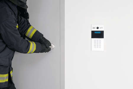 a fireman's hand tries to open a locked door with an electronic lock