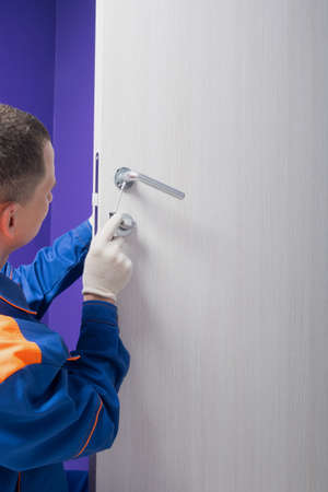 worker in uniform, fixing the door lock, there is a place for the inscription Standard-Bild