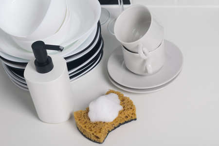 on a white table, washed dishes, plates, mugs, and on a sponge foam for disinfection Standard-Bild