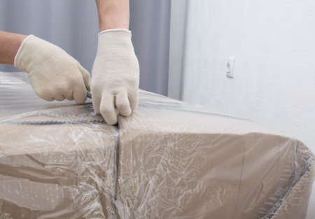 close-up of the delivery man's hands, cut the dense polyethylene, to protect the cardboard from moisture Standard-Bild