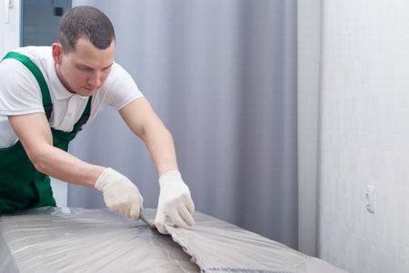 deliverer, cuts dense polyethylene, to protect the cardboard from moisture Standard-Bild