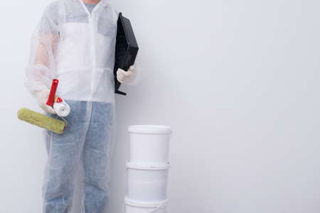 a man in protective clothing, with paint rollers in his hands, put three buckets on top of each other, against the background of a white wall, there is a place for the inscription