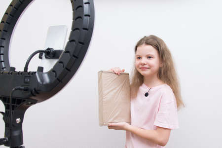 a girl blogger, in front of a circular light and a smartphone, makes a review of the package for unpacking