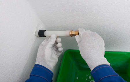 in a plastic pipe, a worker in protective gloves installs a copper adapter for plumbing Standard-Bild