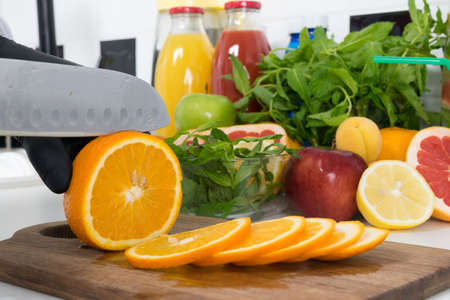 close-up of slicing ripe oranges, slices, with a knife by the chef's hands