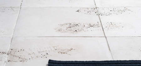 on the white tile floor, shoe marks after the street, background