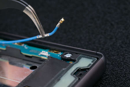 close-up of disconnecting the contact wire with tweezers, phone repair, antenna Standard-Bild