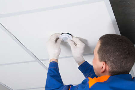 close-up of the installation of a motion sensor for lighting automation, with hands in protective gloves of an electrician