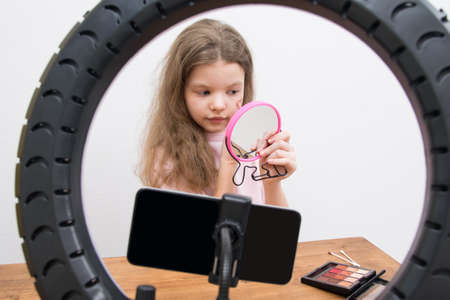 in the center of a circular lamp and a smartphone, a blogger girl makes a make-up, draws a heart on her cheek Standard-Bild