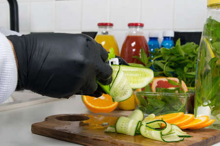 the chef's hands in black gloves, cut into thin slices of cucumber to add to a vitamin cocktail
