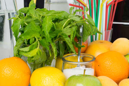 a set of fruits and herbs for making drinks in a jug and a glass with sugar, close-up