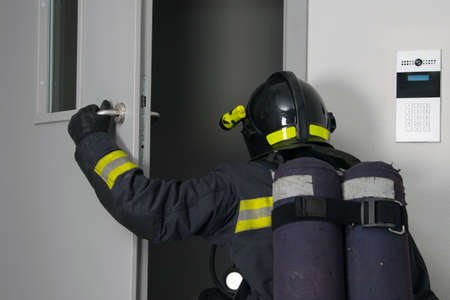 a firefighter in protective clothing and a hard hat, with fire extinguishing equipment, enters the doorway, rear view