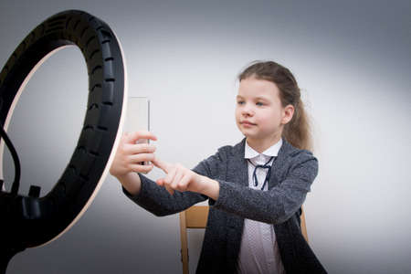 girl blogger, takes a selfie, in front of a ring lamp