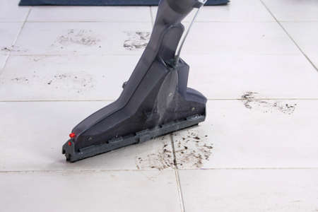 on the white tile, a washing vacuum cleaner removes dirty footprints from shoes Standard-Bild