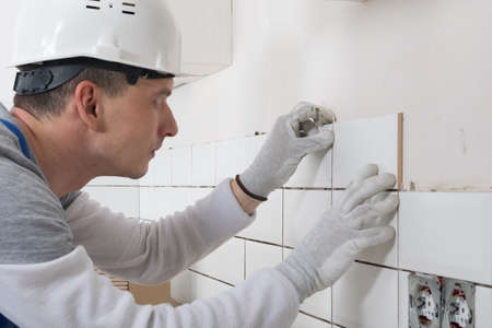 a construction worker in a protective helmet, applies a white tile to the wall, close-up Standard-Bild