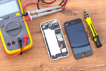 on a wooden table there is an electric tester equipment and a phone with a removed liquid crystal screen to replace it