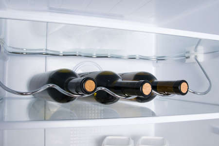 there are three bottles of wine on the shelf of the white refrigerator