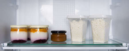 on the glass shelf of the refrigerator, there are cans of yogurt and fruit and grainy cottage cheese in plastic boxes Standard-Bild