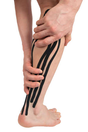 two hands wrapped around the calf muscle of the right leg with a black kinesio tape pasted on, to relieve the load after sports and during