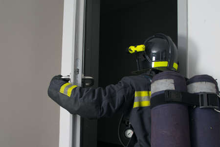 a firefighter in protective clothing and a hard hat, with fire extinguishing equipment, enters the doorway, rear view, close-up