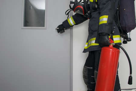 firefighter in protective clothing and with a fire extinguisher, opens the iron door, there is a place for the inscription