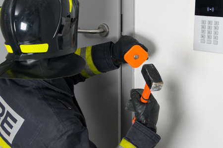 close-up of a firefighter in protective clothing and a hard hat trying to open a door with a sledgehammer and chisel