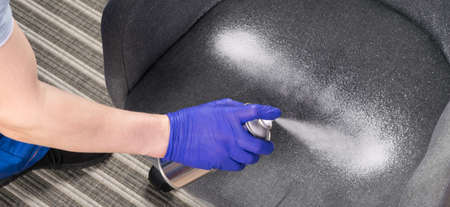 close-up of cleaning a gray chair with a can of white foam Standard-Bild