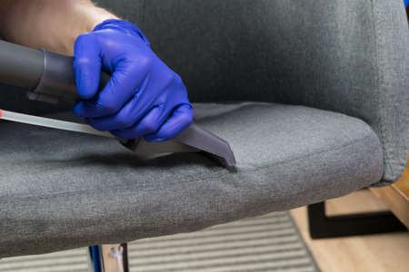 wet cleaning of the chair with a cleaning vacuum cleaner, hand in protective gloves, close-up