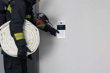 a firefighter in protective clothing, with fire extinguishing equipment, tries to open a closed door by dialing the intercom code, there is a place for the inscription
