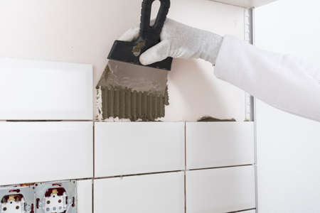 the process of applying white tiles to the wall, an iron spatula is applied to the solution