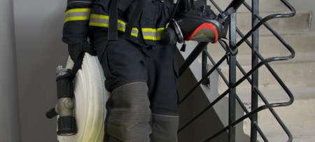 fireman, holding water handling equipment, barrel and hoses
