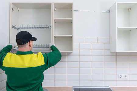 installation master, storage systems in the kitchen, inserts a grid for storing dishes in hanging cabinets, rear view