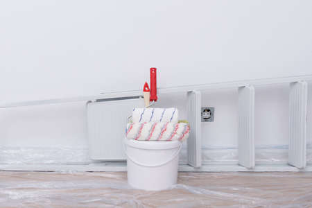 on a white background, building materials, a bucket of paint, rollers and a stepladder