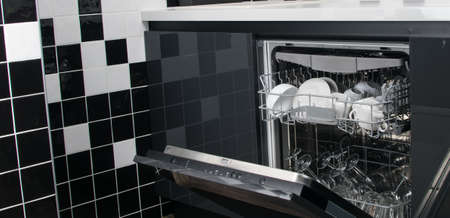 against the background of the black and white kitchen, the open door of the dishwasher with clean plates and mugs