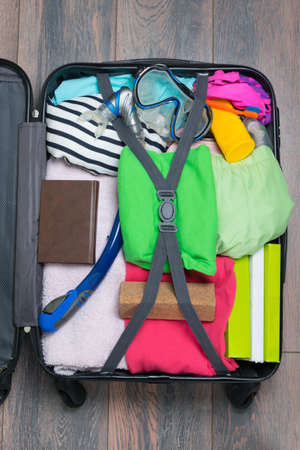 a set of things for travel and recreation, in an open suitcase, on a wooden background
