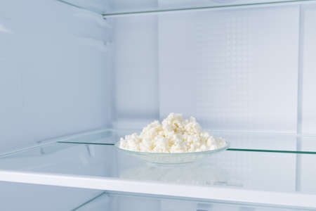 grainy cottage cheese in a plate, in the refrigerator on a glass shelf, on a white background