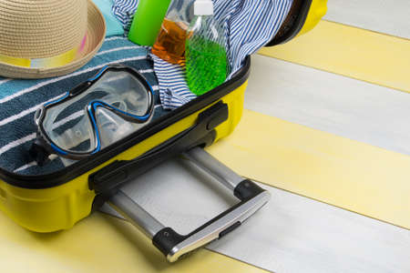 on a yellow-gray background, an open suitcase for traveling and a set of items for relaxing in it, a towel, a swimsuit, a hat, a diving mask and sunscreen, there is a place for the inscription