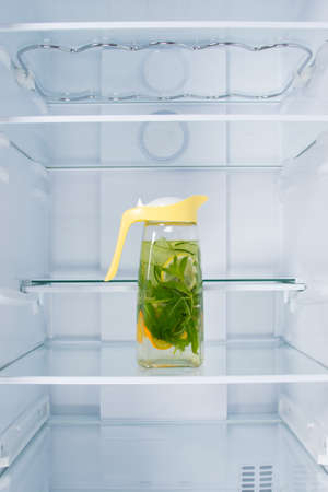 lemonade in a jug of citrus and mint, in the refrigerator, on a glass shelf, on a white background Standard-Bild