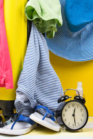 on a gray-yellow background, a set for travel and recreation, a suitcase, a sundress, flip-flops, a hat, glasses and an alarm clock