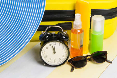 against the background of a yellow suitcase, there is a set of items for travel and recreation, sunscreens, glasses, a hat and an alarm clock