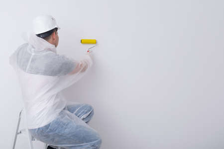 a construction worker in protective clothing and a hard hat, smoothes the wallpaper on the white wall with a special roller, there is a place for the inscription