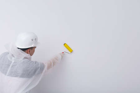 a construction worker in protective clothing and a helmet, smoothes the wallpaper on the white wall with a special roller, there is a place for the inscription, a rear view Standard-Bild