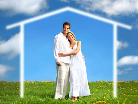 real estate house: Young love couple smiling under blue sky.  Real estate concept