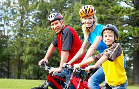ni�os en bicicleta: Happy family. Padre, madre e hijo a caballo en el parque