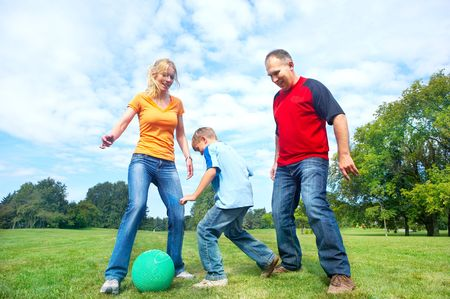 babies playing: Happy family. Father, mother and sons playing football  in the park  Stock Photo